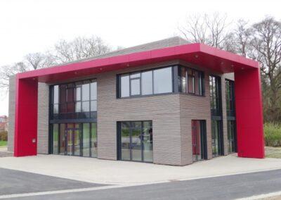 Vordachbekleidung mit roten HPL Fundermaxxplatten und Dachabdichtung mit Gefällewärmedämmung und Elastomerbitumen-Schweissbahnen in Dörentrup